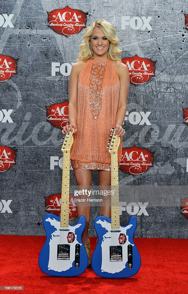Singer Carrie Underwood poses in the press room with her awards for Female Artist of the Year and Single by a Vocal Collaboration during the 2012 American Country Awards at the Mandalay Bay Events Center on December 10, 2012 in Las Vegas, Nevada.