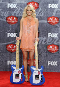 Singer Carrie Underwood poses in the press room with her awards for Female Artist of the Year and Single by a Vocal Collaboration during the 2012...