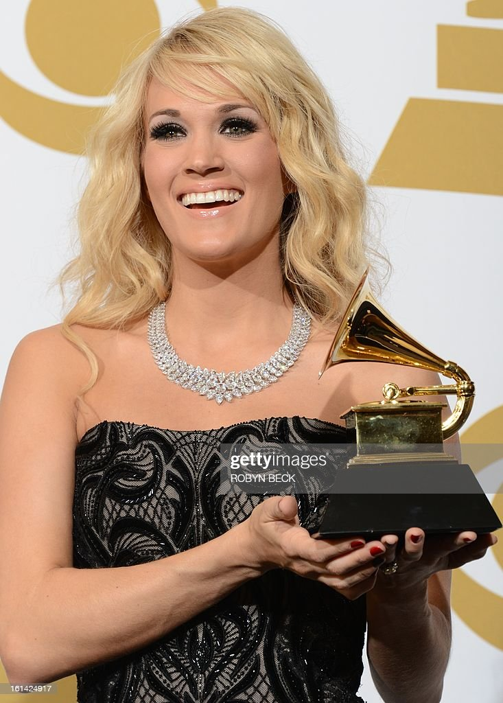 Singer Carrie Underwood poses in the press room with her trophy for best Country song for 'Stronger' at the Staples Center during the 55th Grammy Awards in Los Angeles, California, February 10, 2013. AFP PHOTO Robyn BECK