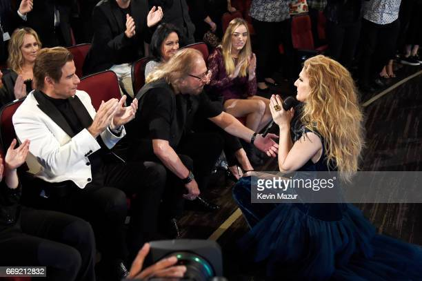 Singer Celine Dion performs as actor John Travolta and honoree Barry Gibb of the Bee Gees look on from the audience during 'Stayin' Alive A GRAMMY...