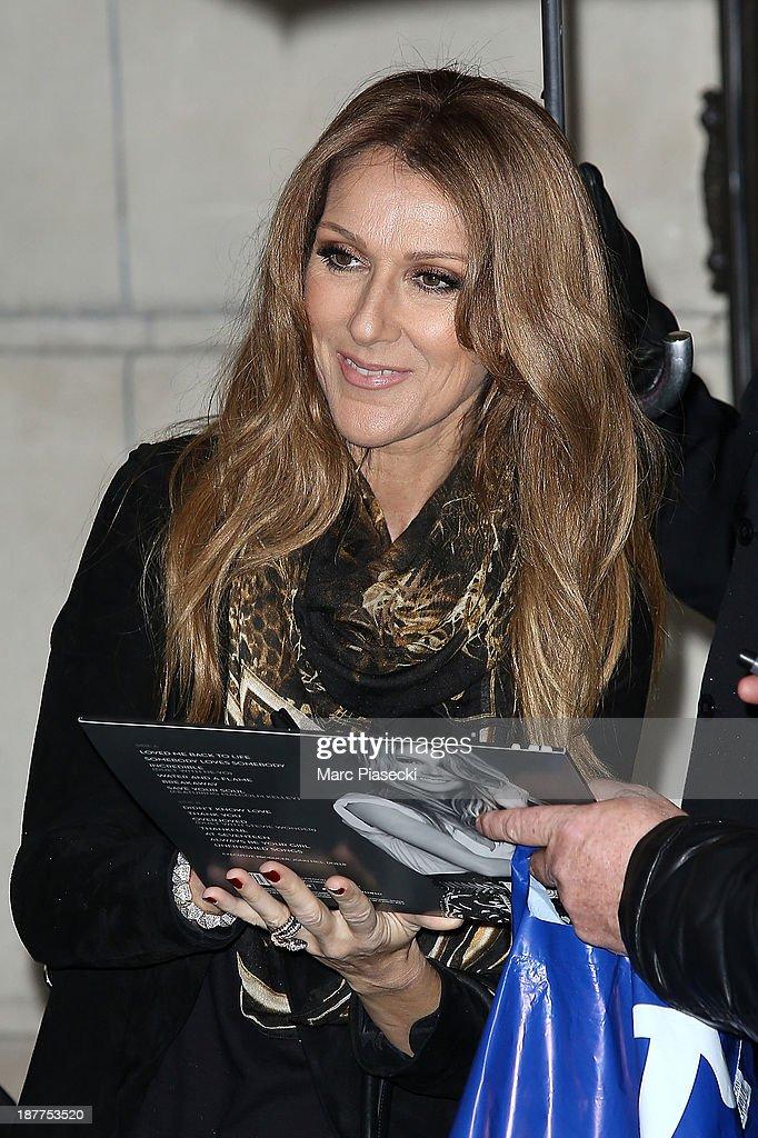 Singer Celine Dion signs autographs as she leaves her hotel on November 12, 2013 in Paris, France.