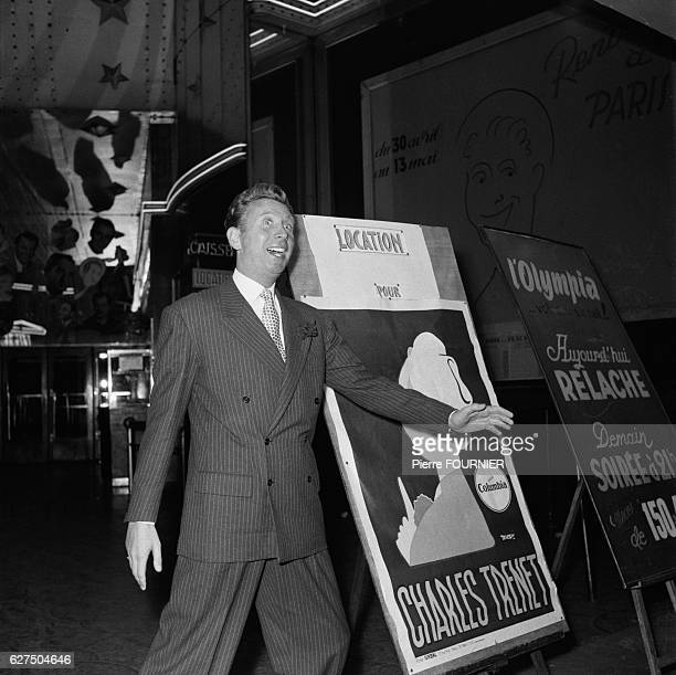 Singer Charles Trenet stands next to a poster advertising his forthcoming tour at the Olympia music hall
