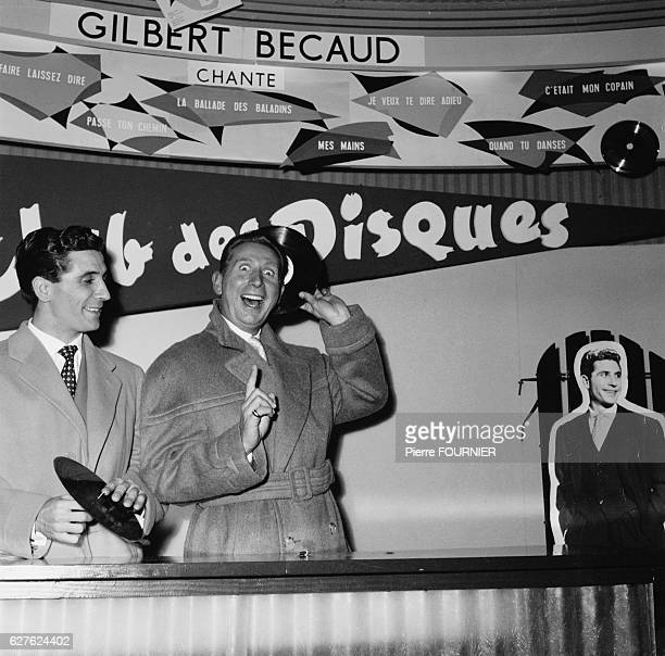 Singer Charles Trenet stands next to a poster advertising his forthcoming tour at the Olympia music hall alongside Gilbert Becaud