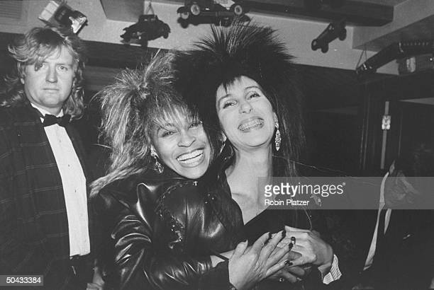 Singer Cher Bono sporting braces on her teeth happily getting hugged by singer Tina Turner as Turner's mgr Roger Davies looks on at MTV awards party