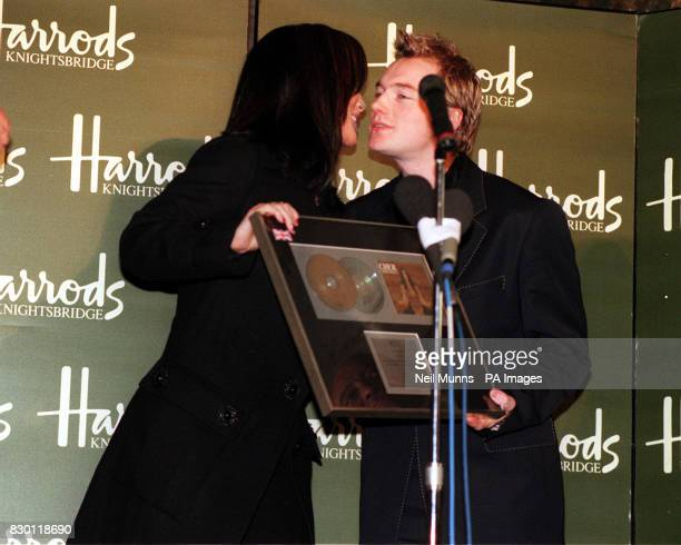 Singer Cher kisses 'Boyzone' singer Ronan Keating at the Harrods store in Knightsbridge London as he presents her with a Gold Disc after she...