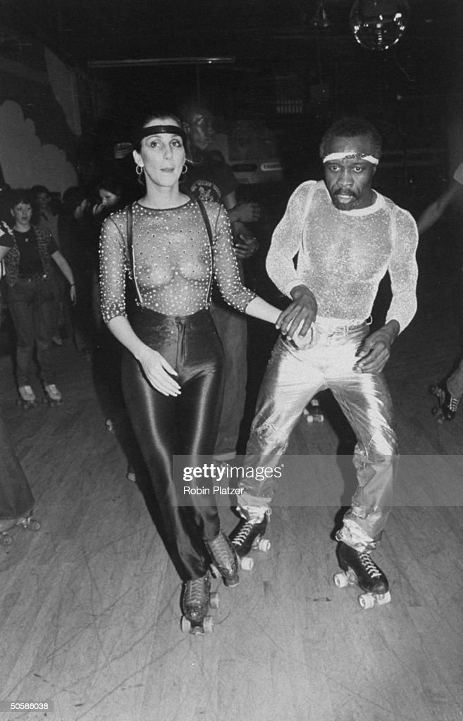 Singer Cher wearing long spandex pants seethrough blouse and headband skating at Empire Rink w Bill Butler during party for Casablanca Records