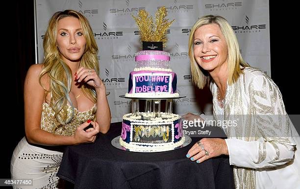 Singer Chloe Lattanzi and her mother singer/actress Olivia NewtonJohn pose with a celebratory cake as they celebrate the 35th anniversary of 'Xanadu'...