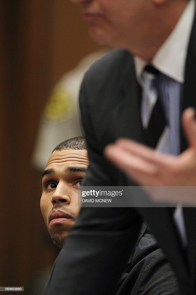 Singer Chris Brown looks up at his attorney Mark Geragos as he appears in court for a probation progress report hearing on February 6, 2013 in Los Angeles, California. Brown pleaded guilty to assaulting his girlfriend, singer Rihanna, after a pre-Grammy Awards party in 2009. Prosecutors have alleged that he has failed to meet the terms of his probation. AFP PHOTO / POOL / DAVID MCNEW