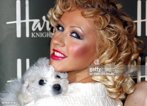 US singer Christina Aguilera kisses Bichon Frise Lucy as she officially opens the Harrods Summer Sale at the worldfamous department store in...