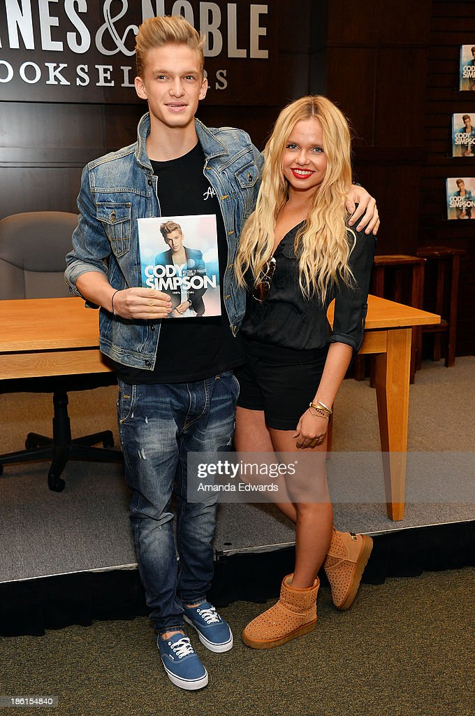 Singer <a gi-track='captionPersonalityLinkClicked' href=/galleries/search?phrase=Cody+Simpson&family=editorial&specificpeople=7068455 ng-click='$event.stopPropagation()'>Cody Simpson</a> (L) and his sister, actress <a gi-track='captionPersonalityLinkClicked' href=/galleries/search?phrase=Alli+Simpson&family=editorial&specificpeople=7439624 ng-click='$event.stopPropagation()'>Alli Simpson</a> pose before Cody signs copies of his new book 'Welcome To Paradise' at Barnes & Noble bookstore at The Grove on October 28, 2013 in Los Angeles, California.