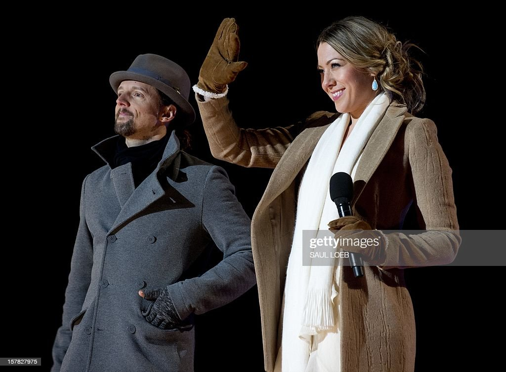 Singer Colbie Caillat (R) waves alongside singer Jason Mraz after performing together during the National Christmas Tree Lighting on the Ellipse adjacent to the White House in Washington, DC, on December 6, 2012. The annual event, hosted by Actor Neil Patrick Harris, features US President Barack Obama and performances by Jason Mraz, Ledisi, James Taylor, Kenny 'Babyface' Edmonds, Colbie Caillat and American Idol season 11 winner Phillip Phillips. AFP PHOTO / Saul LOEB