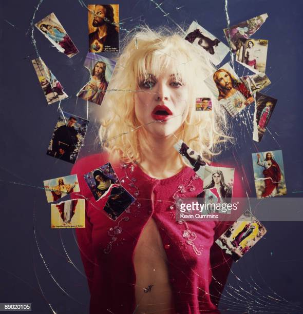 Singer Courtney Love of American rock group Hole surrounded by torn devotional pictures of Jesus the Virgin Mary Saint Sebastian and others circa 1995