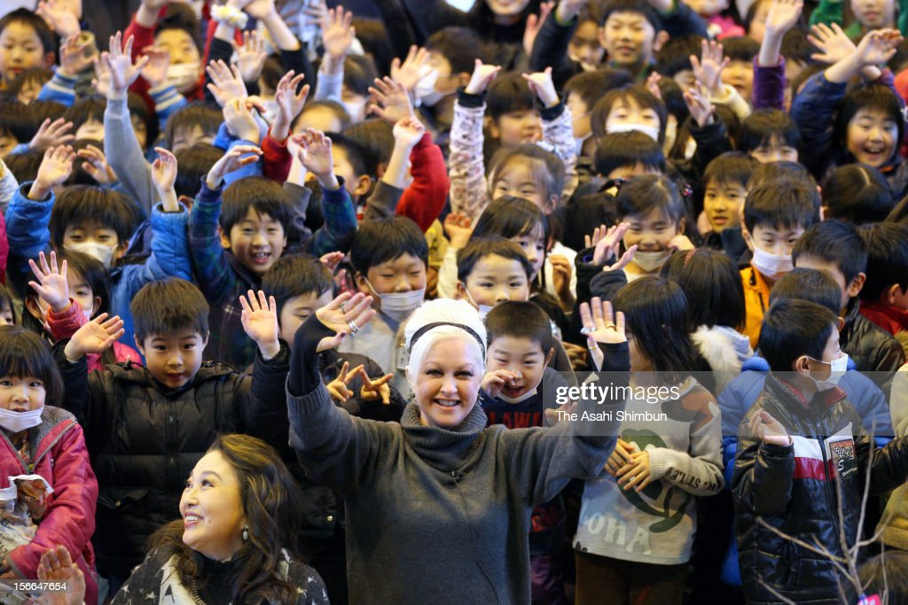 U.S. singer Cyndi Lauper poses for photographs with school pupils on her visit to Okaido Elementary School on March 5, 2012 in Ishinomaki, Miyagi, Japan. Lauper, who arrived Japan when the Great East Japan Earthquake hit the regions last year, continues charity concerts and presented the cherry blossom young trees to the school.