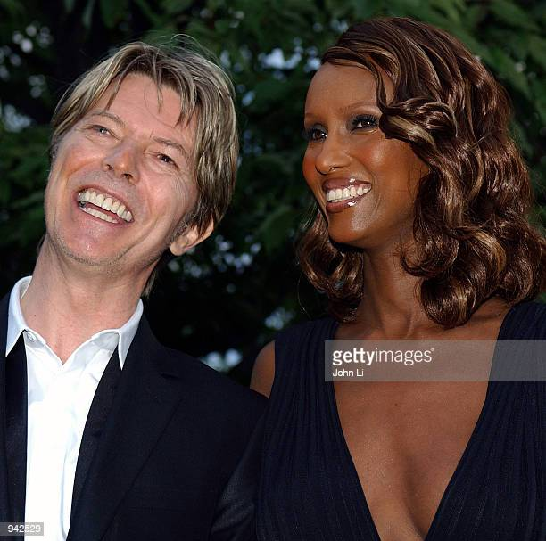 Singer David Bowie and his wife Iman attend the Serpentine Gallery Summer Party at the Serpentine Gallery in Kensington Gardens July 9 2002 in London...