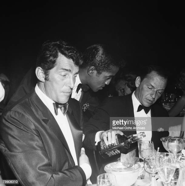 Singer Dean Martin and Sammy Davis Jr sit at a table as fellow singer and Rat Pack member Frank Sinatra pours Jack Daniels from a bottle at the...
