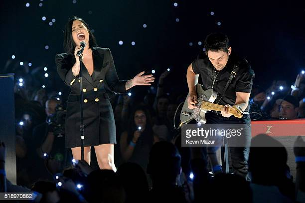 Singer Demi Lovato and musician Brad Paisley perform onstage at the iHeartRadio Music Awards which broadcasted live on TBS TNT AND TRUTV from The...