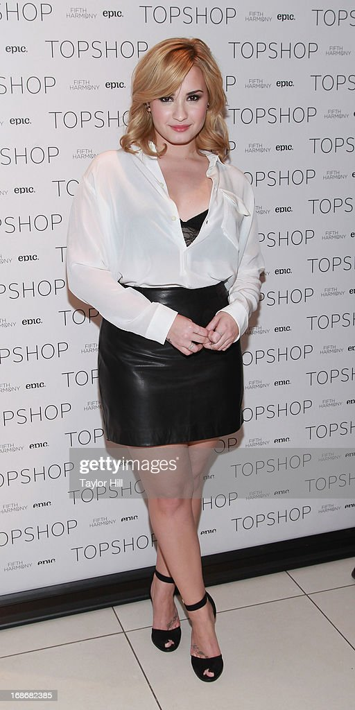 Singer Demi Lovato attends a photocall with Fifth Harmoney at TopShop SoHo on May 13, 2013 in New York City.