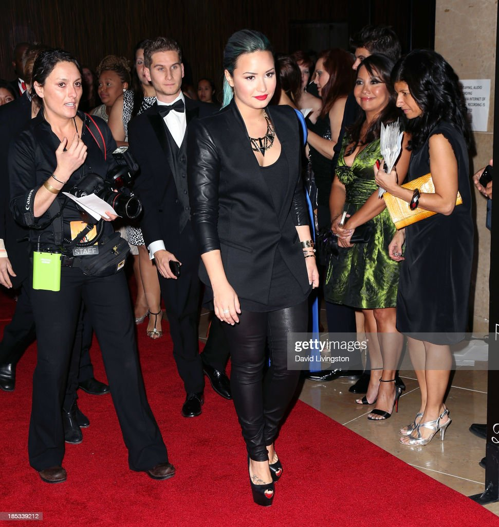 Singer Demi Lovato (C) attends the launch of the Redlight Traffic app at the Dignity Gala at The Beverly Hilton Hotel on October 18, 2013 in Beverly Hills, California.