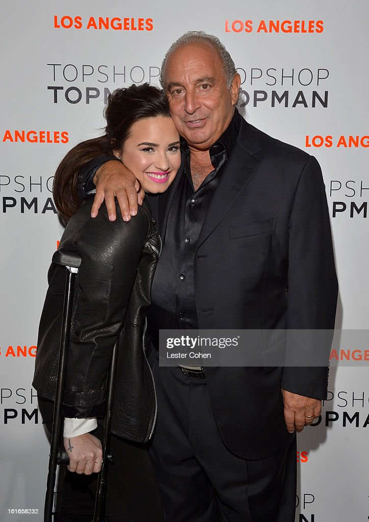 Singer Demi Lovato wearing Topshop (L) and proprietor Sir Philip Green arrive at the Topshop Topman LA Opening Party at Cecconi's West Hollywood on February 13, 2013 in Los Angeles, California.
