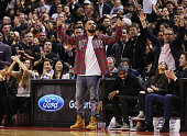 Singer Drake celebrates a Raptors score on 'Drake Night' during an NBA game between the Cleveland Cavaliers and the Toronto Raptors at the Air Canada...