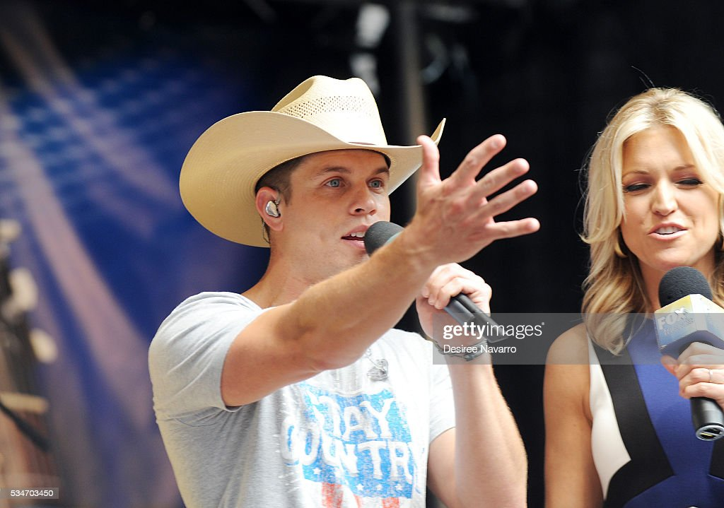 Singer <a gi-track='captionPersonalityLinkClicked' href=/galleries/search?phrase=Dustin+Lynch&family=editorial&specificpeople=8612719 ng-click='$event.stopPropagation()'>Dustin Lynch</a> (C) appears on stage with TV personality Ainsley Earhardt during 'FOX & Friends' All American Concert Series outside of FOX Studios on May 27, 2016 in New York City.