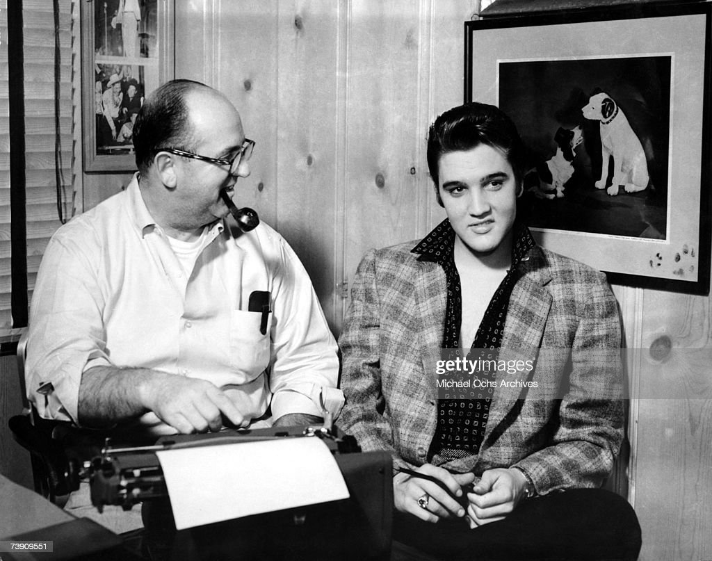 Singer Elvis Presley and his manager Colonel Tom Parker sit at a typewriter in front of the a picture of the RCA Victor Dog in circa 1956 in Memphis...