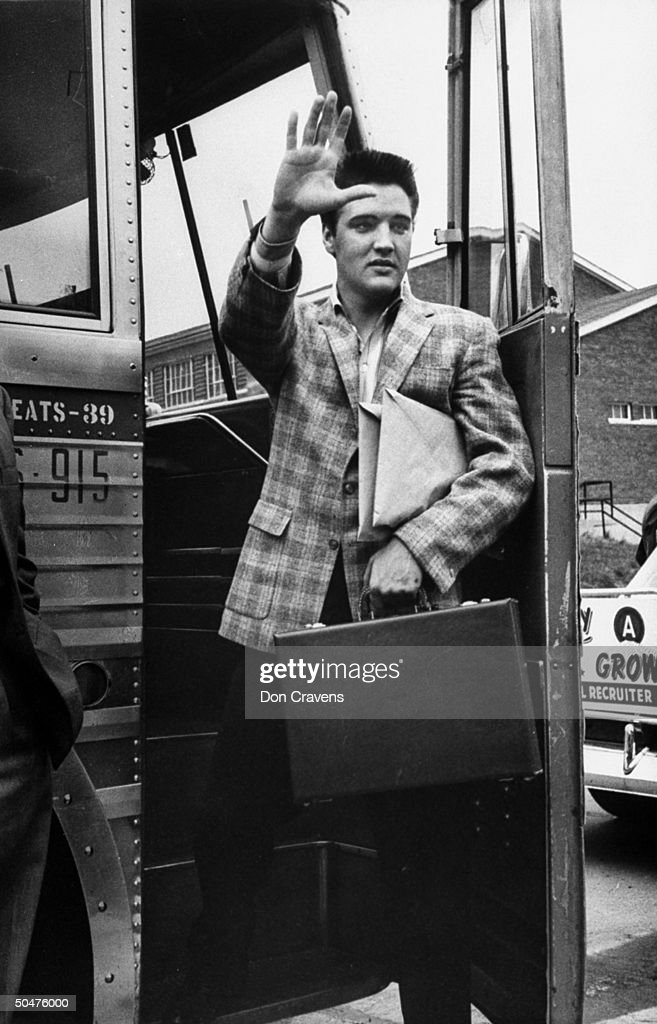 Singer Elvis Presley holding briefcase as he waves goodbye to his parents & girlfriends fr. doorway of bus he is boarding on his way to the Army in Ft. Chaffee following his induction.