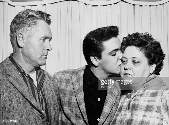 Singer Elvis Presley kisses his mother Gladys on the eve of his induction into the Army At left is his father Vernon