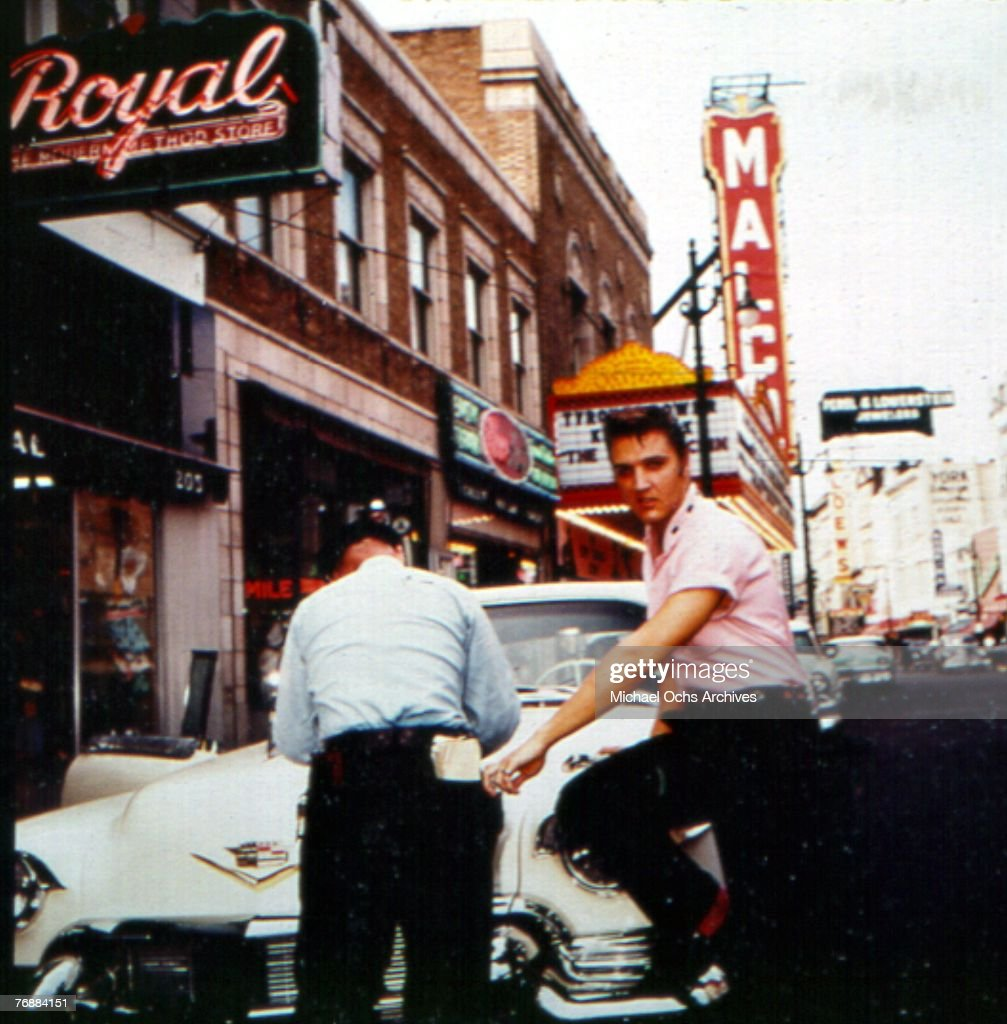 Singer Elvis Presley leans against his Cadillac as he gets a parking ticket on Main Street outside of Jim's Barber Shop in 1956 in Memphis, Tennessee.
