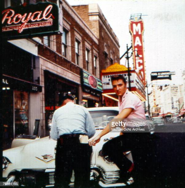Singer Elvis Presley leans against his Cadillac as he gets a parking ticket on Main Street outside of Jim's Barber Shop in 1956 in Memphis Tennessee