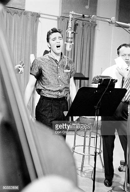 Singer Elvis Presley recording song in studio