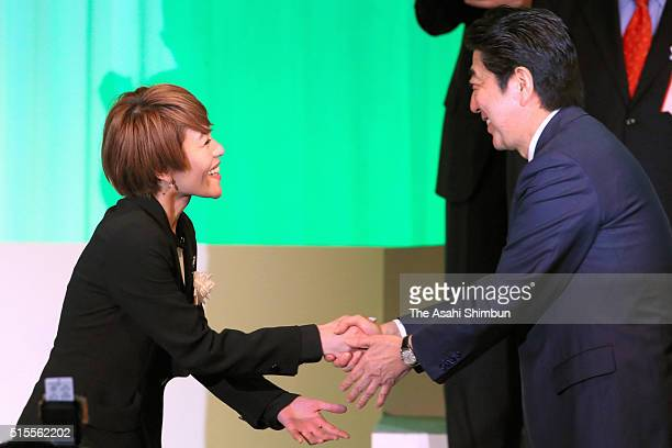 Singer Eriko Imai who will run for the candidacy in the this summer's upper house election shakes hands with Prime Minister Shinzo Abe during the...