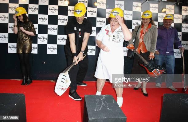 Singer 'Evil' Jared Hennagan smashes a guitar as singer Amy Macdonald and Rita Gilligan look on at the Hard Rock Cafe Berlin reopening on April 28...