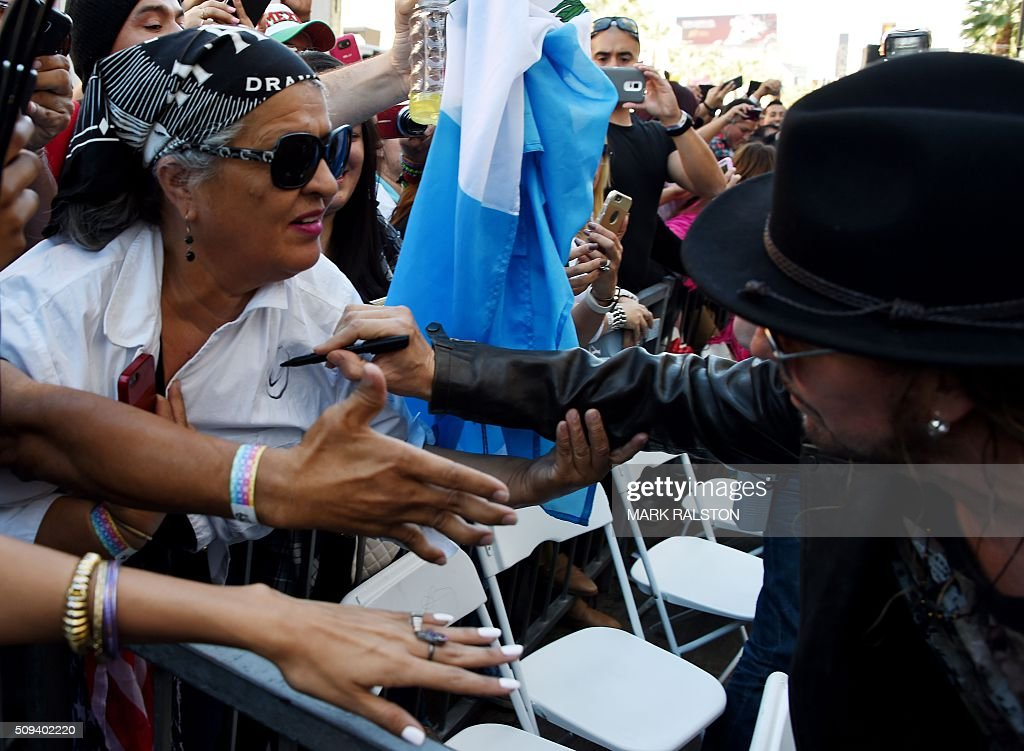 Singer Fher Olvera from the rock band 'Mana' signs a fans shirt at the ceremony honoring them with the 2,573rd star on the Hollywood Walk of Fame in Hollywood, California on February 10, 2016. / AFP / Mark Ralston