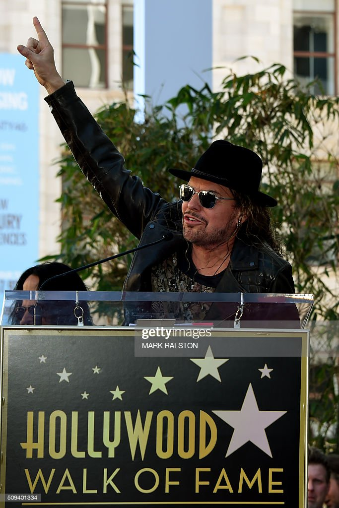 Singer Fher Olvera from the rock band 'Mana' waves to fans at the ceremony honoring them with the 2,573rd star on the Hollywood Walk of Fame in Hollywood, California on February 10, 2016. / AFP / Mark Ralston