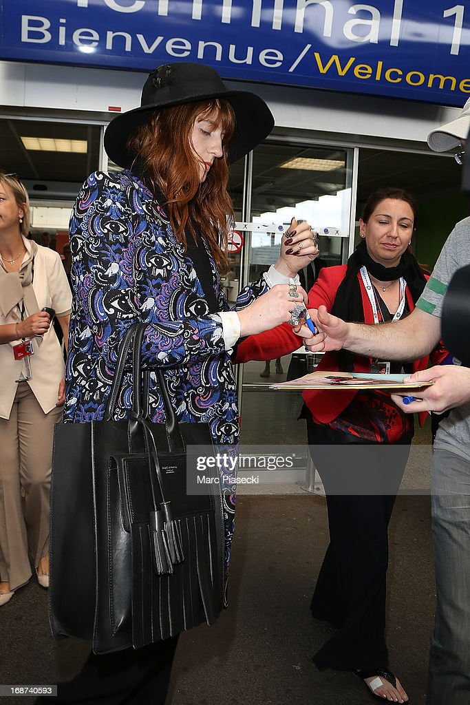Singer Florence Welch signs autographs as she arrives at Nice airport on May 14, 2013 in Nice, France.