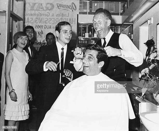 Singer Frankie Vaughan is watched by a laughing crowd as television personality Bruce Forsyth takes over from barber Gay Buccheri on his haircut at...