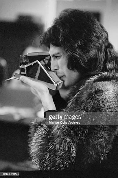 Singer Freddie Mercury of British rock band Queen takes a Polaroid circa 1977