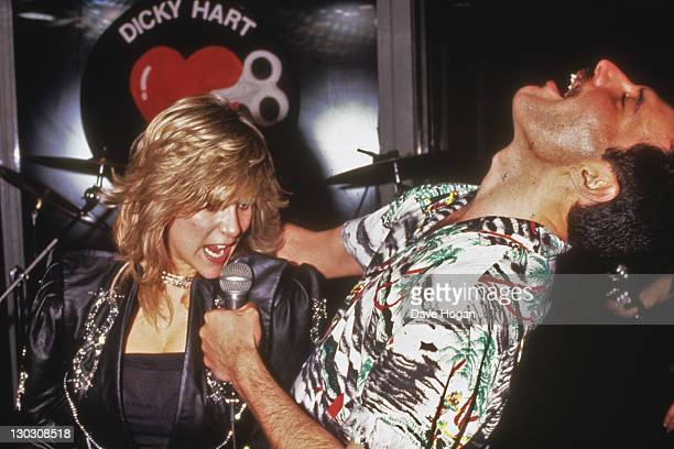 Singer Freddie Mercury of Queen performs a duet with Samantha Fox during a party at Kensington Roof Gardens in London 12th July 1986 The event is an...