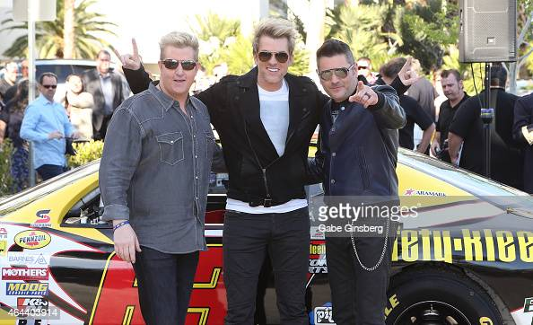 Singer Gary LeVox guitarist Joe Don Rooney and bassist Jay DeMarcus of the band Rascal Flatts pose after arriving by NASCAR race cars at the Hard...