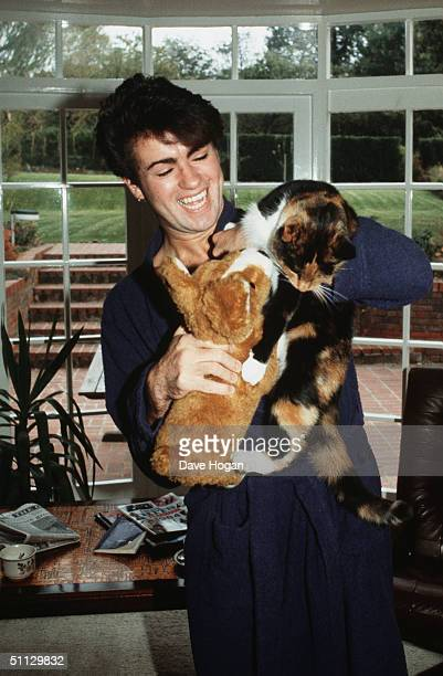 Singer George Michael poses at home with his cat after losing his voice and being forced to cancel a number of live shows in 1980 London