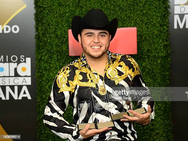 Singer Gerardo Ortiz poses in the pressroom with the awards for Male Artist of the year Songs Artist of the year Norteno Artist of the year and...