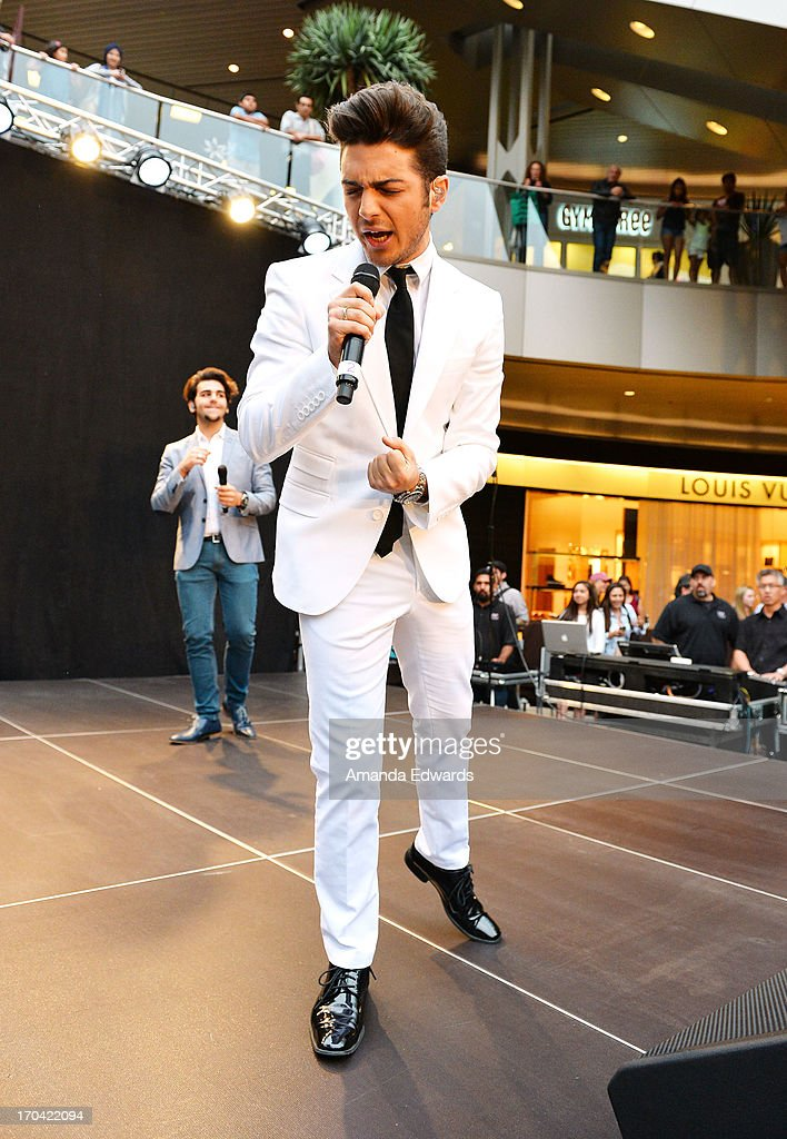 Singer Gianluca Ginoble (R) of the group Il Volo performs onstage before signing copies of their new album 'We Are Love' at Santa Monica Place on June 12, 2013 in Santa Monica, California.