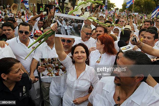 Singer Gloria Estefan holds aloft a photograph of Cuba's Las Damas de Blanco as she along with her husband Emilio Estefan and others march in support...