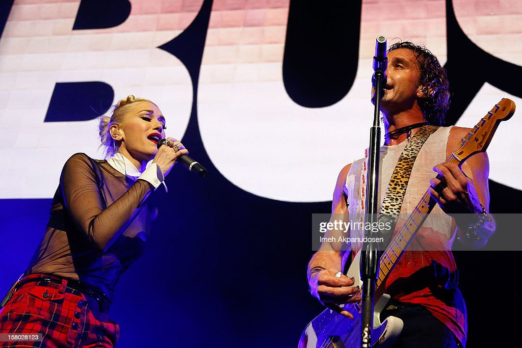 Singer Gwen Stefani (L) makes a surprise appearance, performing onstage with her husband, musician Gavin Rossdale of Bush at the 23rd Annual KROQ Almost Acoustic Christmas at Gibson Amphitheatre on December 8, 2012 in Universal City, California.