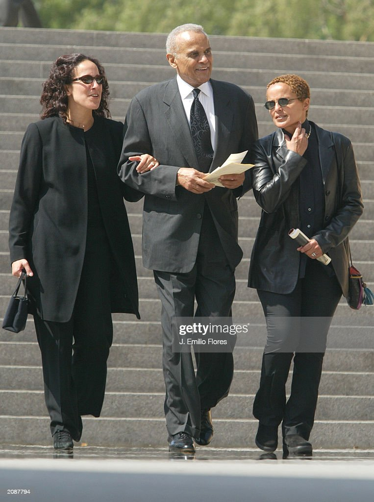 Singer Harry Belafonte (C) with daughters, Gina Belafonte (L) and Sheri Belafonte-Harper, as they leave the Mass Memorial for actor Gregory Peck June 16, 2003 in Los Angeles, California. The public memorial mass was held a the Our Lady of Angels Cathedral in Downtown Los Angeles.