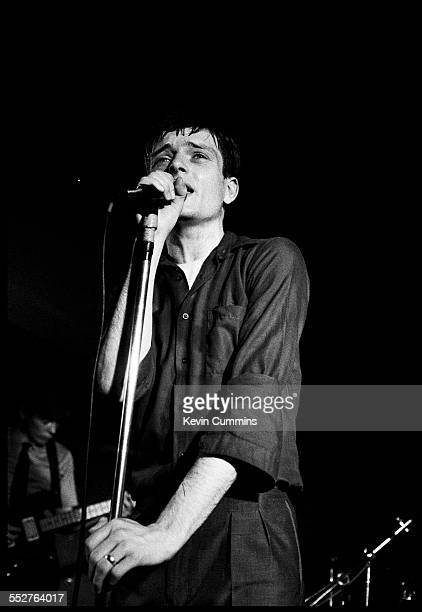 Singer Ian Curtis performing with English rock group Joy Division at the Russell Club also known as The Factory Manchester 1979 In the background is...
