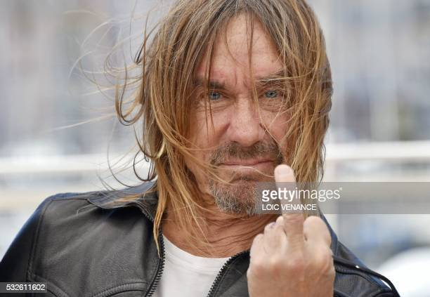 TOPSHOT US singer Iggy Pop gives the fingers while posing on May 19 2016 during a photocall for the film 'Gimme Danger' at the 69th Cannes Film...