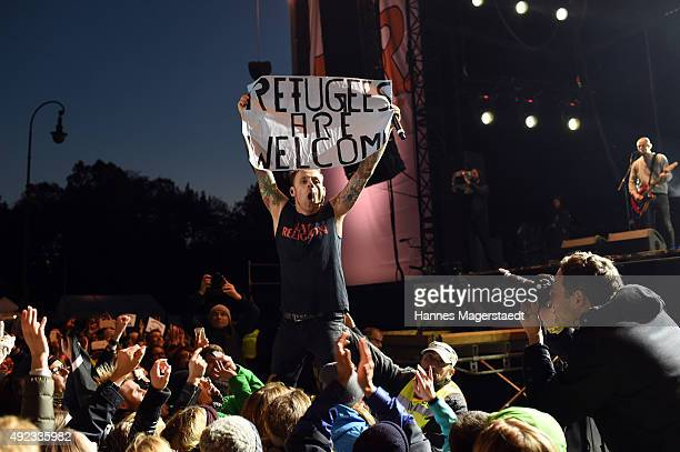 Singer Ingo Knollmann of 'Donots' poses with a placard 'Refugees Are Welcome' during the WIR open air at Koenigsplatz on October 11 2015 in Munich...