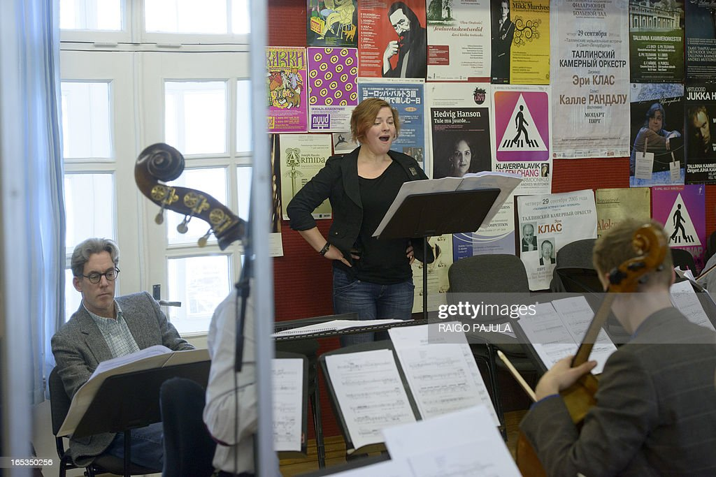 Singer Iris Oja (C) performs with members of the Tallinn Chamber Orchestra and Scott Diel (L, seen in the mirror), author of the libretto, during a rehearsal of the opera 'Nostra Culpa' on April 3, 2013 in Tallinn, Estonia. US composer Eugene Birman turned into an opera a Twitter feud between the Estonian President Toomas Hendrik Ilves and New York Times columnist Paul Krugman who questioned the impact of Estonia's austerity measures. The short opera in two movements and using two voices will be first performed during Tallinn Music Week on April 7, Birman, who moved from Riga to the US at age of six, told AFP. AFP PHOTO / RAIGO PAJULA